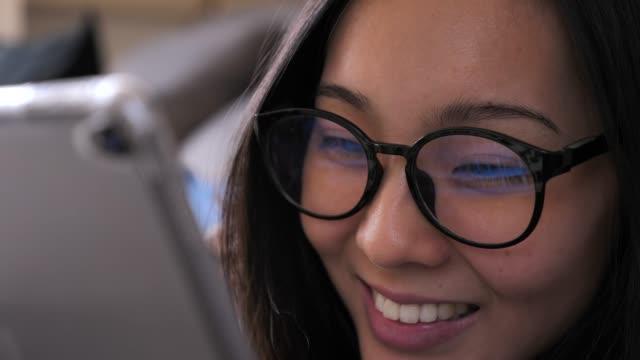 vídeos y material grabado en eventos de stock de mujer asiática que busca en la tableta pc en casa - mujer bella