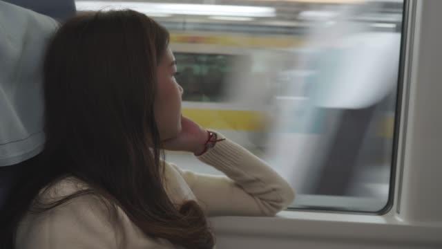 Asiatische Frau schaut durch das Zugfenster nach draußen