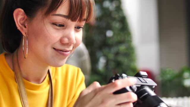 vidéos et rushes de image de regard de femme asiatique sur l'appareil-photo - designer