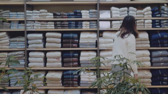 stockvideo's en b-roll-footage met aziatische vrouw op zoek door kleding rek met haar zoon. - kledingrek