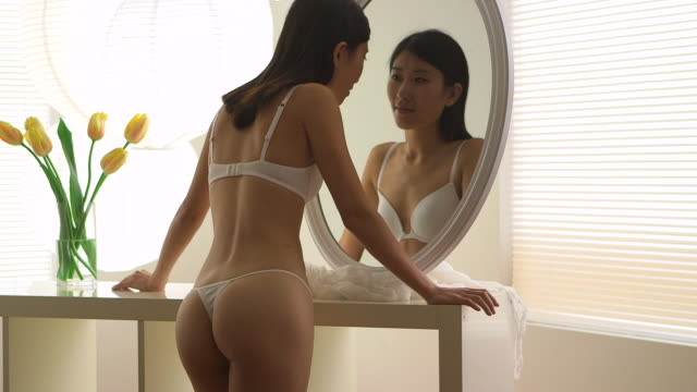 asian woman looking through mirror - only young women stock videos and b-roll footage