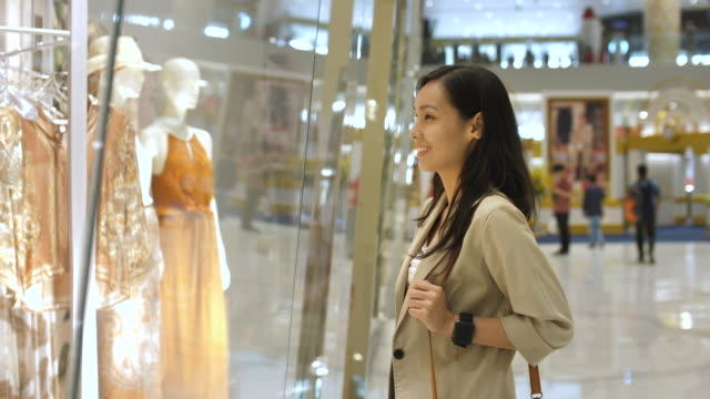 asian woman looking through the store window - window display stock videos & royalty-free footage