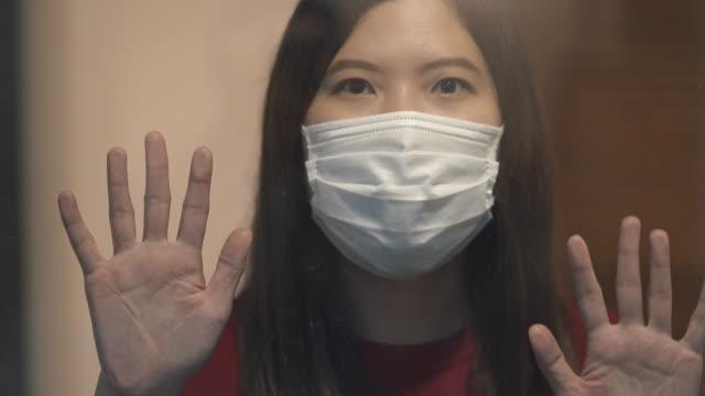 コロナウイルスまたはcovid-19のための窓の自己検疫を見ているアジアの女性 - ホームレス点の映像素材/bロール