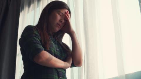 stockvideo's en b-roll-footage met aziatische vrouw die door vensterzelf-quarantaine voor coronavirus kijkt - solitair