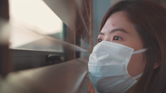 asian woman looking through window self-quarantine for coronavirus - fear stock videos & royalty-free footage