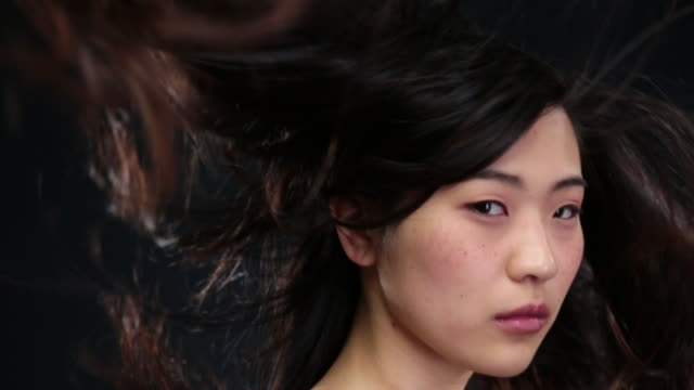 vídeos de stock, filmes e b-roll de cu slo mo asian woman looking up hair moving in wind / london, greater london, united kingdom - exposto pelo vento