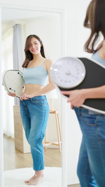 アジアの女性は鏡で見る - 低炭水化物ダイエット点の映像素材/bロール