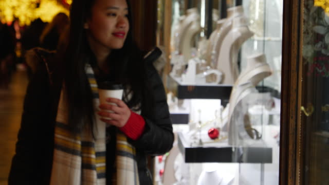 vidéos et rushes de asian woman looks into store window and walks on. - désir
