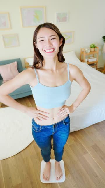 アジアの女性は幸せに体重を減らす - 低炭水化物ダイエット点の映像素材/bロール