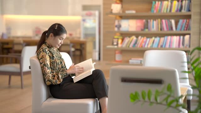 donna asiatica amore leggere libri stare in biblioteca per leggere i libri che ami come hobby. - letteratura video stock e b–roll