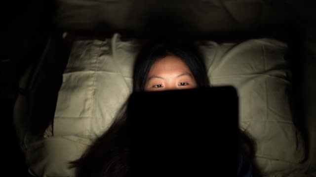 asian woman lying on back in dark bedroom using digital tablet - lying on back stock videos & royalty-free footage