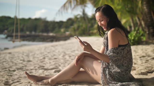 asian woman lying on white sand beach and using app on smartphone - getting away from it all stock videos and b-roll footage