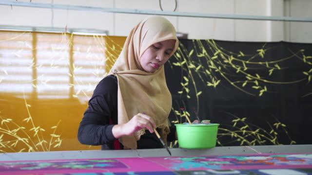 Asian woman making batik in a workshop