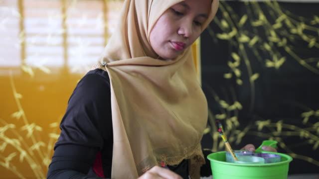 asian woman making batik in a workshop - batik stock videos and b-roll footage