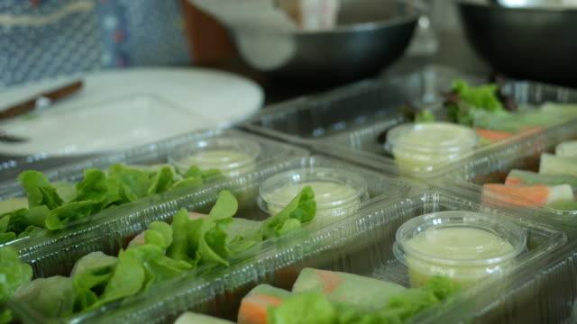 キッチンでロール野菜サラダを作るアジアの女性、家庭産業のコンセプト - デリカッセン点の映像素材/bロール