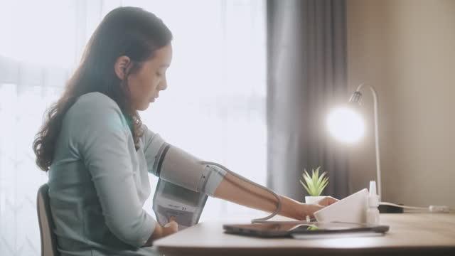 vídeos y material grabado en eventos de stock de asian woman mide su propia presión arterial con dispositivo digital de presión arterial - colesterol