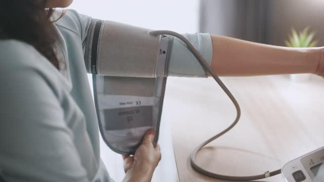 asian woman misura la propria pressione sanguigna con il dispositivo digitale per la pressione sanguigna - misurare il polso video stock e b–roll