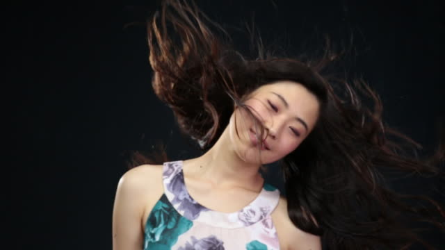 ms slo mo asian woman moving head from side to side smiling, hair moving in wind / london, greater london, united kingdom - greater london video stock e b–roll