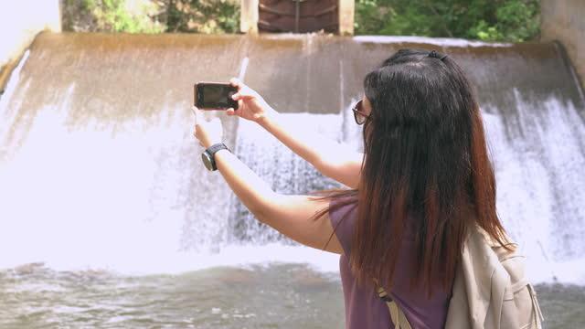 vidéos et rushes de femme asiatique sur de déversoir local dans la scène de l'agriculture non urbaine, chaîne de montagnes, prendre une photo de l'eau flottante comme une cascade, le nord de la thaïlande avec se sentir excité, émotion positive - non urban scene