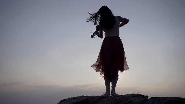 日没時にバイオリンを弾く山の上のアジアの女性. - バイオリン奏者点の映像素材/bロール