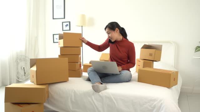 vídeos y material grabado en eventos de stock de mujer asiática venta en línea con su computadora portátil y caja de envío de mensajería en la oficina doméstica en el hogar - recibir