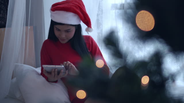 asian woman online shopping on christmas event, panning left video 4k. - santa hat stock videos & royalty-free footage