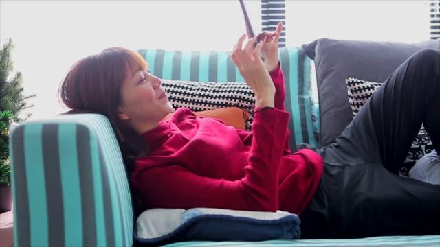 アジアの女性のオンライン ショッピング クリスマス イベントに彼女の携帯電話で - 部屋点の映像素材/bロール