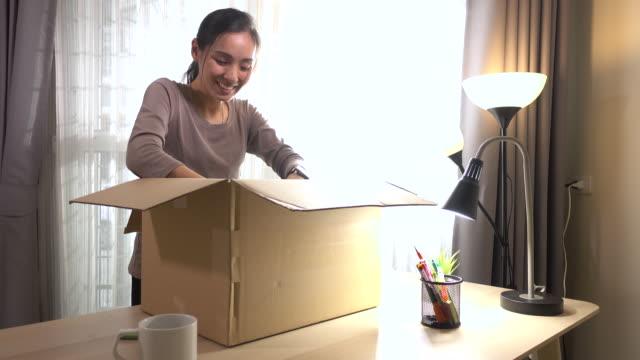 自宅でオンラインショッピングからアジアの女性のオープニングボックス - 段ボール箱点の映像素材/bロール
