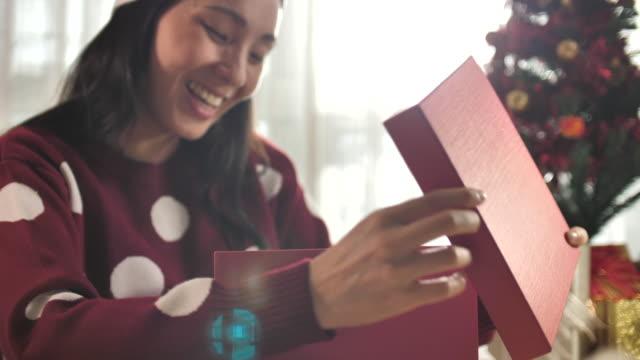 asiatisk kvinna som öppnar julklappslåda hemma - julklapp bildbanksvideor och videomaterial från bakom kulisserna