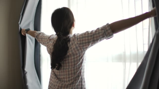 asian woman opening curtain - looking through window stock videos & royalty-free footage
