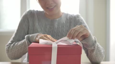 asiatische frau auspacken roten geschenk-box öffnen - image stock-videos und b-roll-filmmaterial