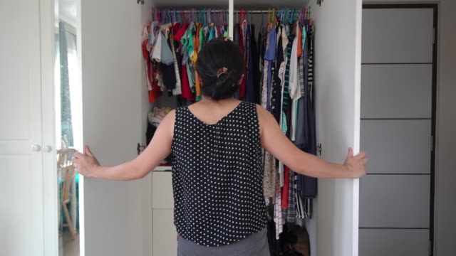 asian woman opening wardrobe and looking the cloth for new alignment - tidy stock videos & royalty-free footage