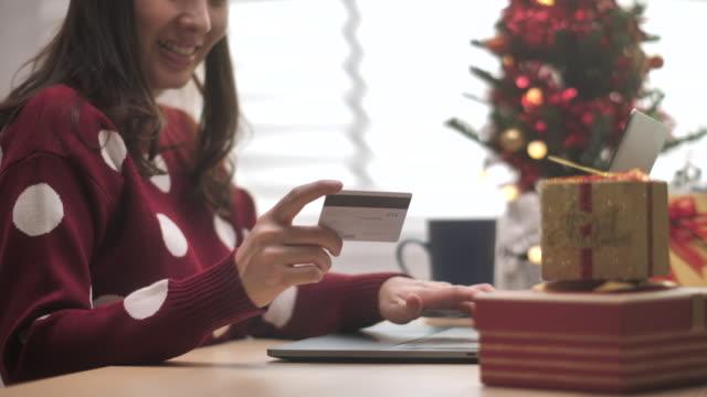 vidéos et rushes de femme asiatique commandant en ligne de son ordinateur portatif avec une carte de crédit dans l'événement de noël - cadeau de noël