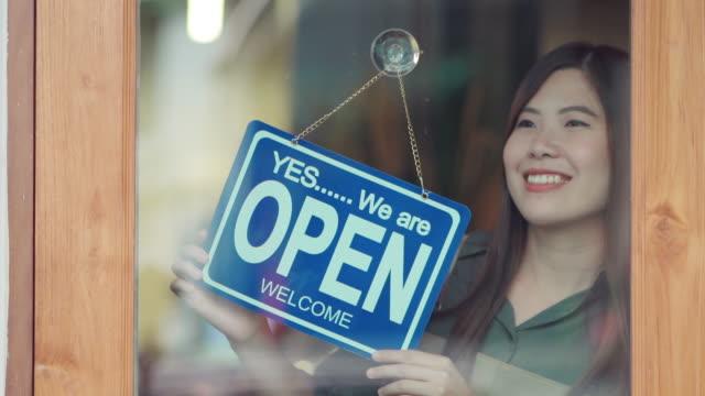stockvideo's en b-roll-footage met aziatische vrouweneigenaar die de koffiewinkel opent - bord open