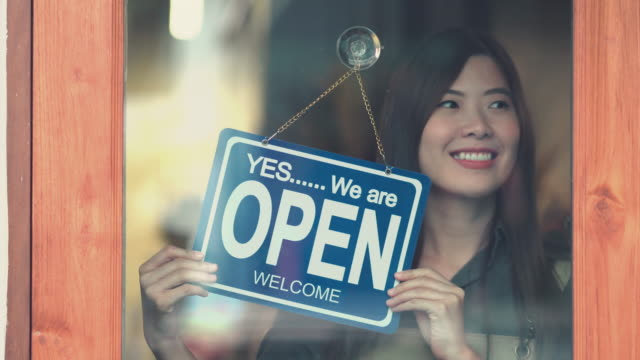 asian woman owner opening the shop - shop sign stock videos & royalty-free footage