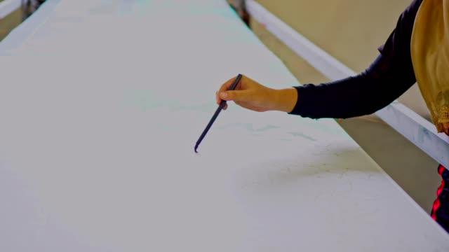 アジアの女性のバティック工房で絹の絵 - トラッキングショット点の映像素材/bロール
