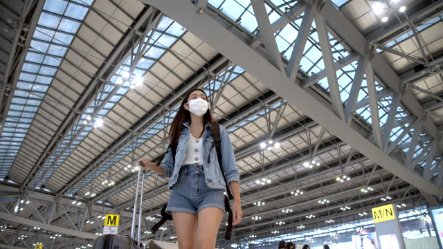 asiatische frau beifahrerin trägt blaue jeans ziehen sie den radkoffer in das beifahrergebäude - flugpassagier stock-videos und b-roll-filmmaterial