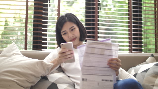 asian woman paying bills online at home - electronic banking stock videos & royalty-free footage