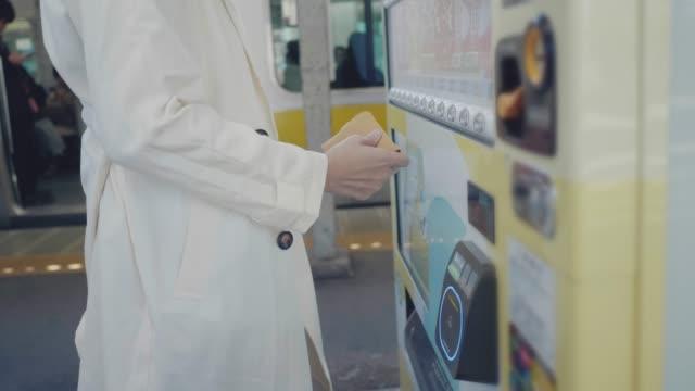 vídeos y material grabado en eventos de stock de mujer asiática pagando con el teléfono inteligente a la máquina expendedora. - pago por móvil