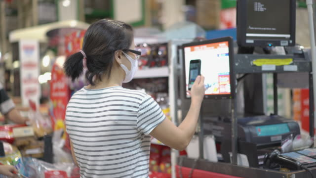 asian woman payment with smartphone at cashier in the supermarket - home shopping stock videos & royalty-free footage