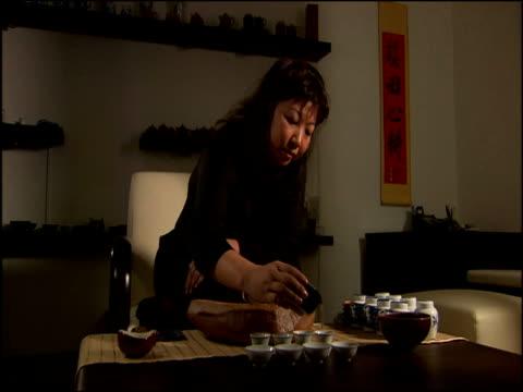 vídeos de stock, filmes e b-roll de asian woman performs tea ceremony at small table with miniature china singapore - pouca luz