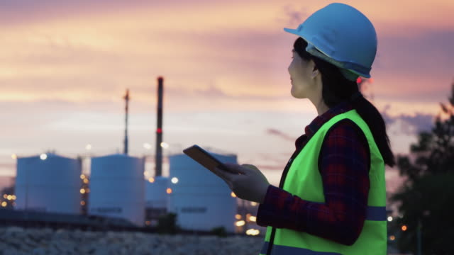 asian woman petrochemical engineer working at night with digital tablet inside oil and gas refinery plant industry factory at night for inspector safety quality control. - inspector stock videos & royalty-free footage