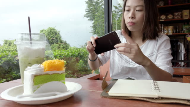 asian woman photographing food and drink in coffee shop. - coffee drink stock videos & royalty-free footage