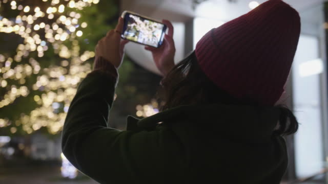 asian woman photographs a city christmas lights. - tradition stock videos & royalty-free footage
