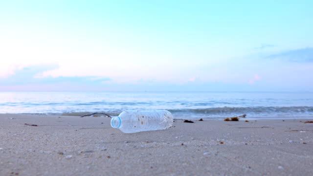 アジアの女性がビーチでプラスチックボトルを拾う - ウォーターボトル点の映像素材/bロール