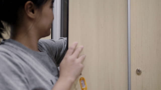 Asian woman placing bag in a locker in gym - Stock video