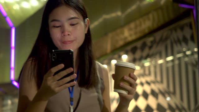 asian woman play mobile, office worker walking outside the office at night - short phrase stock videos & royalty-free footage