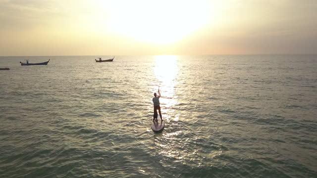 vidéos et rushes de la femme asiatique jouent le paddle board de sup en mer. vue aérienne de la mer claire et des vagues à phuket et baie de phang-nga, thaïlande - baie eau
