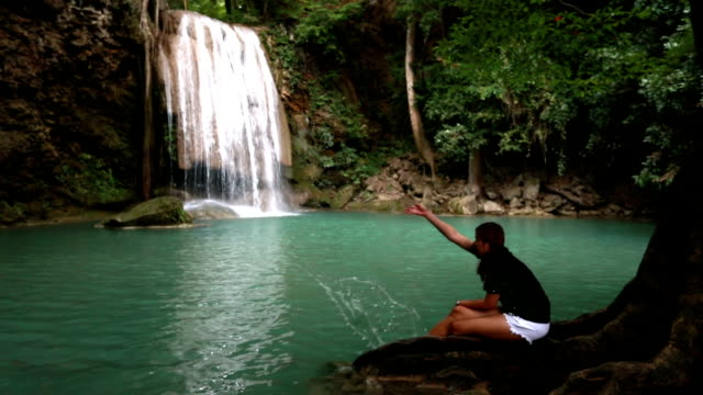 asian woman playing erawan waterfall ,kanchanaburi ,thailand, slow motion - lanci e salti femminile video stock e b–roll