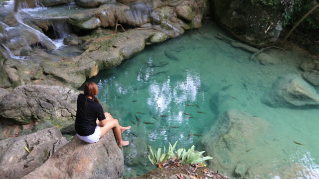 asian woman playing erawan waterfall ,kanchanaburi ,thailand - lanci e salti femminile video stock e b–roll